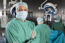 Portrait of a surgeon with his surgical team in the background