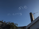 Low angle view of MARRY ME written by vapor trails against blue sky