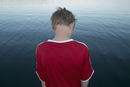Rear view of boy standing against lake