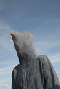 Low angle view of person covered with hood against sky
