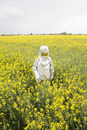 A person in a radiation protective suit standing in an oilseed rape field