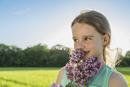 Happy girl smelling purple flowers on field