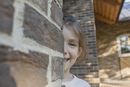 Portrait of smiling girl hiding behind brick wall