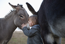 Side view of cute girl kissing donkey on field