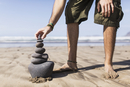 Low section of man balancing stack of stones on beach