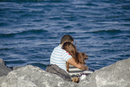Rear view of couple embracing while sitting on rocky sea shore