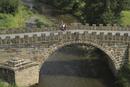 High angle view of woman riding bicycle on bridge