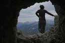 Rear view of woman standing on rock against mountains seen through cave