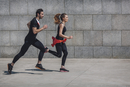 Side view of people jogging on sidewalk by wall