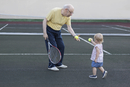 Girl giving tennis ball to grandfather while standing at playing field