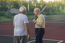 Senior friends carrying tennis rackets while talking at playing field