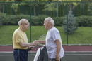 Senior friends shaking hands over net at tennis court