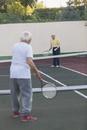 Senior men playing tennis at court