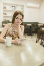 Young woman using phone while having coffee at cafe