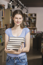 Portrait of smiling woman holding stack of books at library
