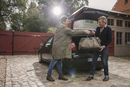 Happy woman giving bag to man by car on driveway