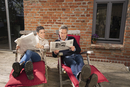 Mature couple reading newspaper while sitting in back yard
