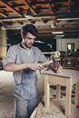 Carpenter hammering nail into wooden stool at workshop