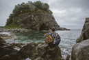 Rear view of hiker sitting on rock formation at beach against sky