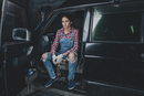 Portrait of confident female mechanic sitting in car at workshop