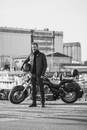 Full length portrait of biker holding helmet while standing by motorcycle against industrial setting