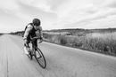 Blurred motion of cyclist riding bicycle on country road by field against sky