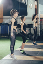 Side view of female athletes exercising with jump ropes at gym