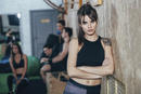 Portrait of confident female athlete standing arms crossed with friends in background at health club
