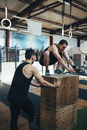 Male athlete assisting friend in doing box jumping at gym