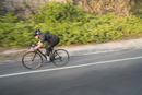 Side view of man cycling on country road
