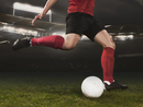 Low section of young soccer player kicking ball on field