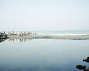 People on sandbar amidst sea against clear sky