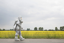 A person in a radiation protective suit walking alongside an oilseed rape field