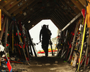 Rear view of man with ski equipment walking out of shed