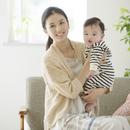 ソファーに座り微笑む母親と赤ちゃん