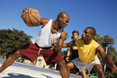 Men playing basketball outdoors
