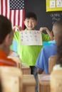 Korean boy showing good grades in class