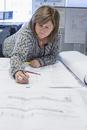 Businesswoman marking blueprints in office