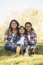 Hispanic sisters smiling in park