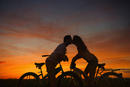 Silhouette of Hispanic couple on bicycles kissing at sunset