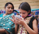 Mother and daughter in Indian clothing using cell phone
