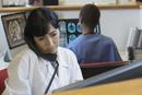 Hispanic doctor talking on telephone in hospital