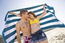 Caucasian couple holding towel on beach