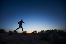 Silhouette of Caucasian teenage boy running at dawn