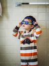 Hispanic boy playing with goggles in bathroom