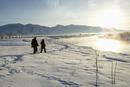 Caucasian couple walking in snowy landscape