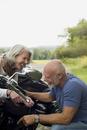 Older couple repairing motorcycle in park
