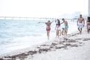 Friends walking in waves on beach