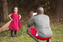 Father taking photograph of daughter in party dress