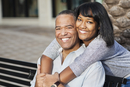 African American father and daughter hugging on bench
